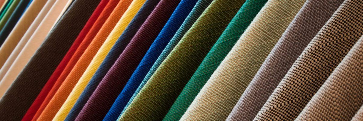 A line of hanging textured fabrics of different colors and shades
